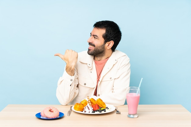 Man at a table having breakfast waffles and a milkshake pointing to the side