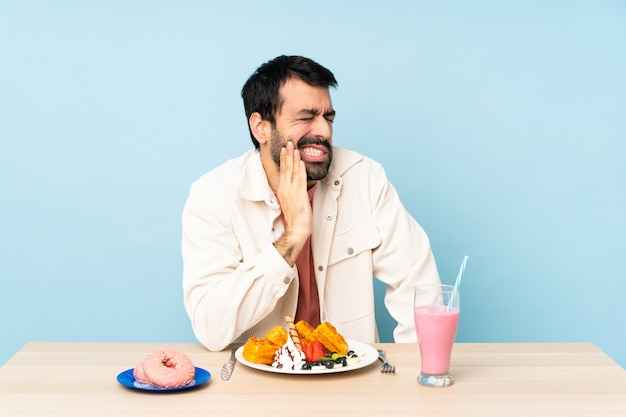 Man at a table having breakfast waffles and a milkshake with toothache