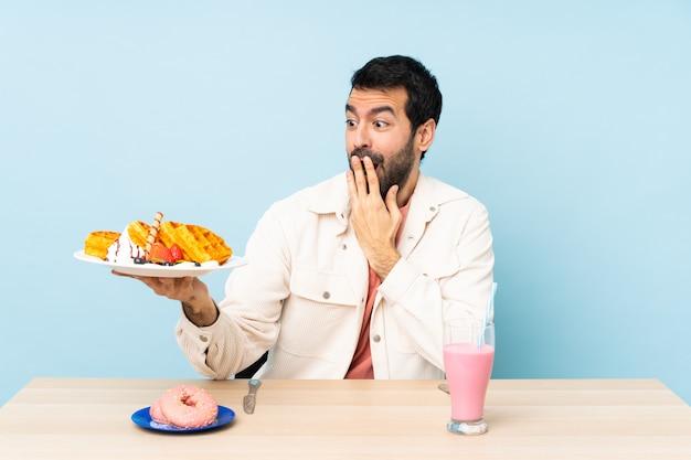 Man at a table having breakfast waffles and a milkshake