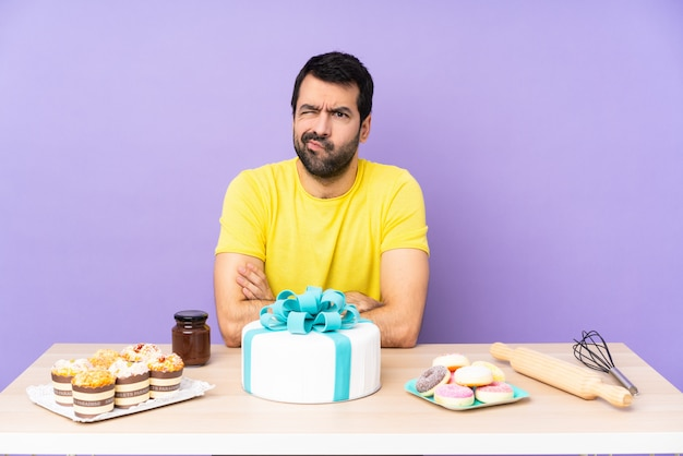 Man in a table with a big cake feeling upset