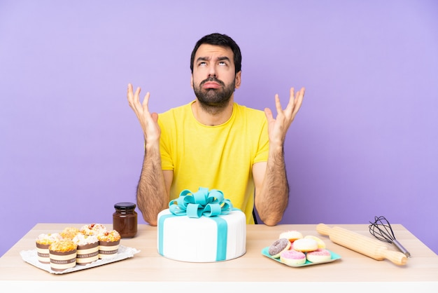 Man in a table with a big cake frustrated by a bad situation