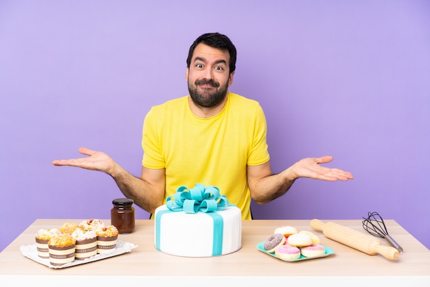 Man in a table with a big cake having doubts while raising hands