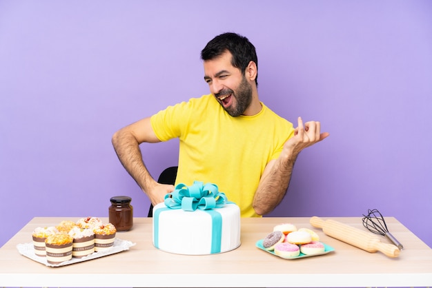 Man in a table with a big cake making guitar gesture