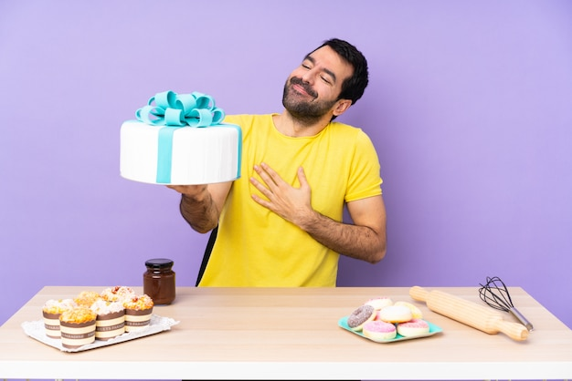Man in a table with a big cake on purple backgroun