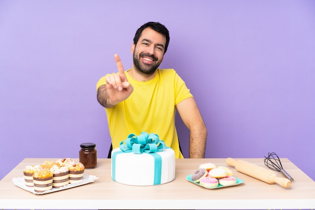Man in a table with a big cake showing and lifting a finger