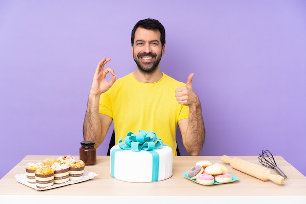 Man in a table with a big cake showing ok sign and thumb up gesture