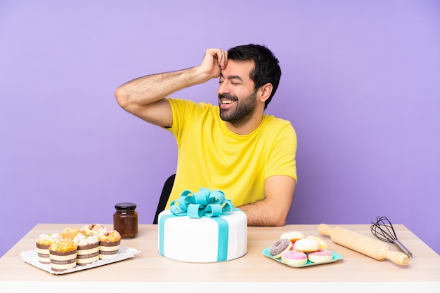 Man in a table with a big cake smiling a lot