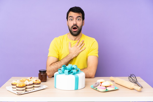 Man in a table with a big cake surprised and shocked while looking right