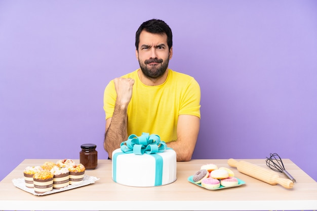 Man in a table with a big cake with angry gesture