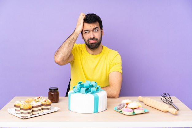 Man in a table with a big cake with an expression of frustration and not understanding