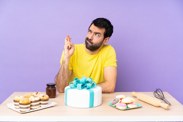 Man in a table with a big cake with fingers crossing and wishing the best