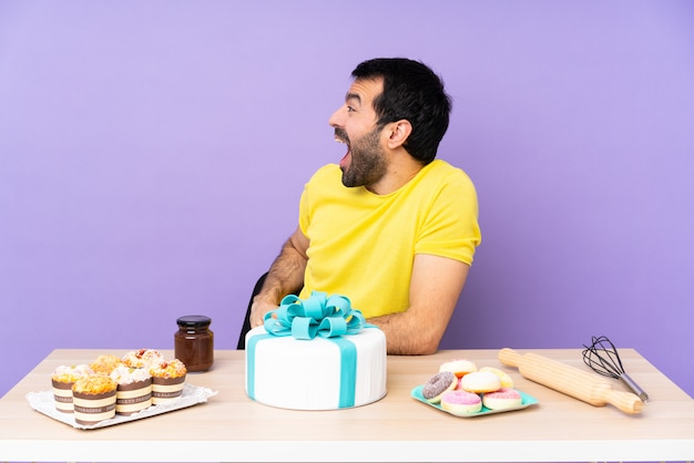 Man in a table with big cake with surprised expression