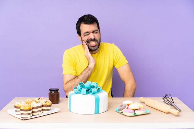 Man in a table with a big cake with toothache