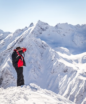 Man tacking picture high up in the mountains