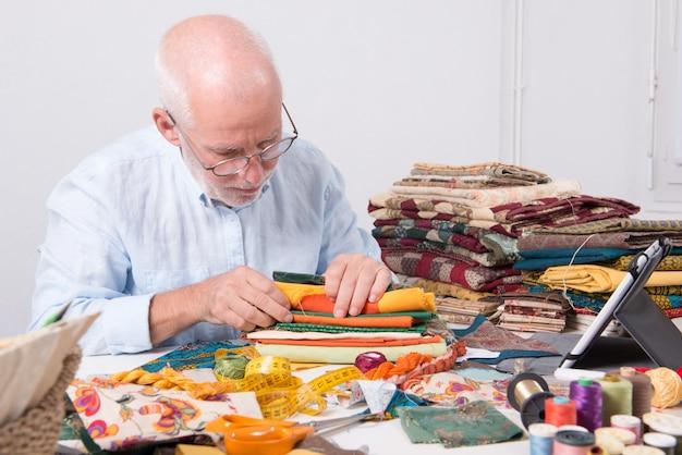 Man tailor choosing fabric