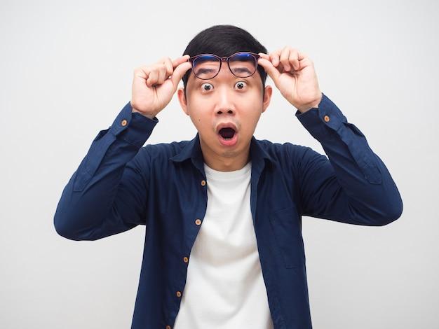 男はショックを受けた感情の白い背景を見て感じて眼鏡を外します