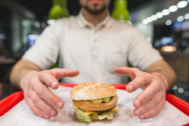 Человек берет большой гамбургер, который стоит на подносе. руки тянутся к вкусному чизбургеру. сосредоточьтесь на гамбургер.