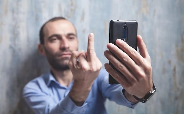 남자는 셀카를 찍고 카메라에서 가운데 손가락을 보여줍니다.