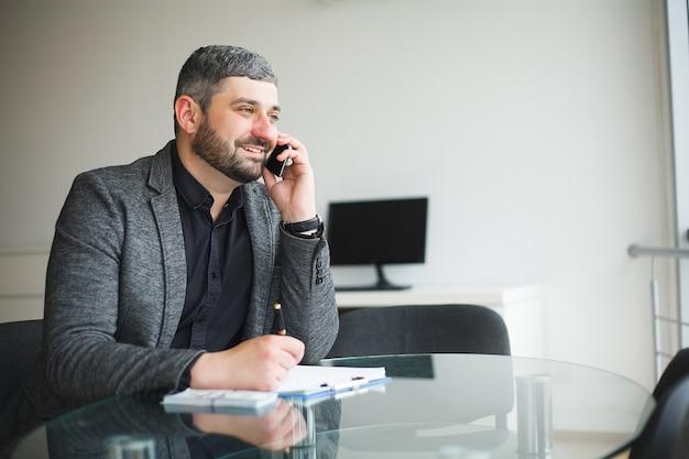 Мужчина берет взятку за подписание контракта и разговаривает по телефону