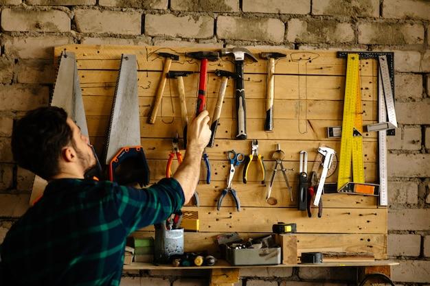 男はツールで壁からハンマーを取る
