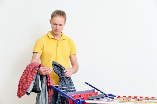 Человек снимает вещи с сушилки для одежды