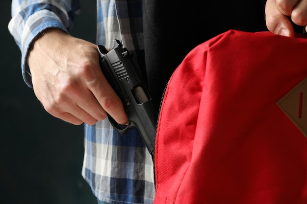 Man takes out a gun from backpack, close up. terrorism