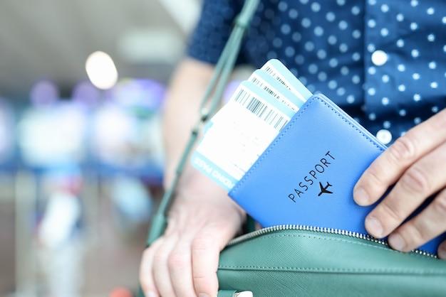男はパスポートで彼のバッグの飛行機のチケットを取り出します