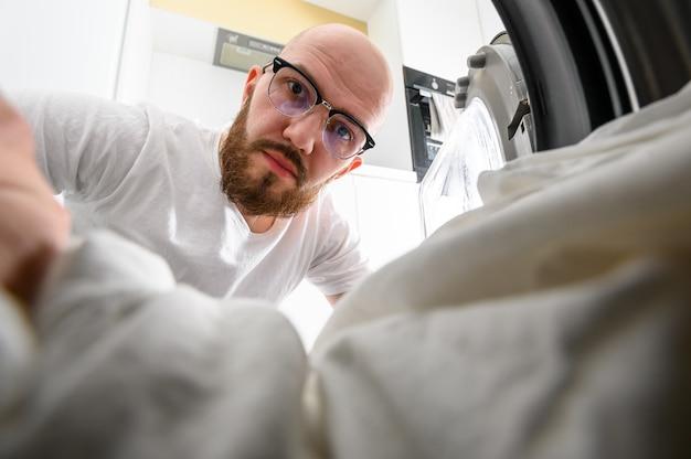 Мужчина достает внутреннюю часть стиральной машины