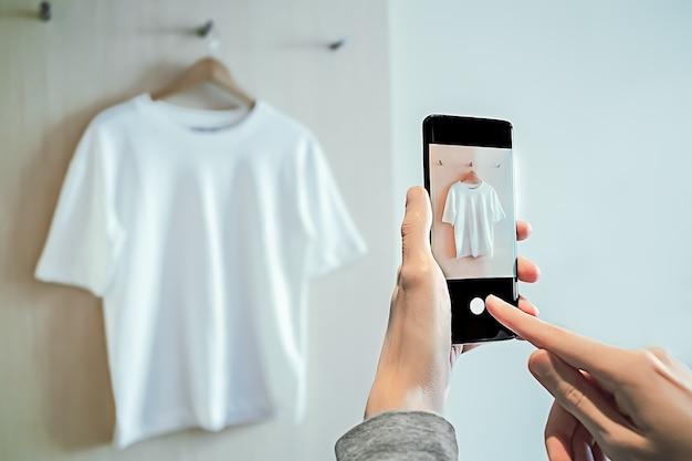 Мужчина фотографирует на смартфоне использованную одежду для перепродажи.