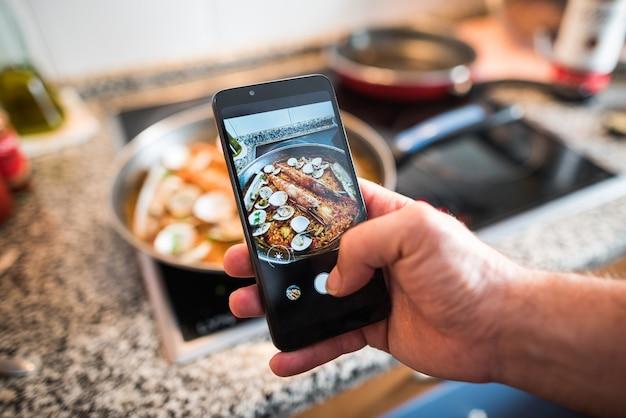 남자는 집에서 스마트폰으로 집에서 만든 빠에야 사진을 찍고 비디오를 만듭니다. 소셜 미디어