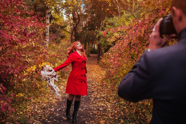 Man takes a picture of his girlfriend using camera in autumn forest