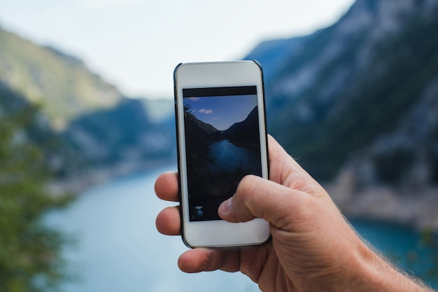 A man takes a picture of mountain landscape on the phone while holding it in one hand