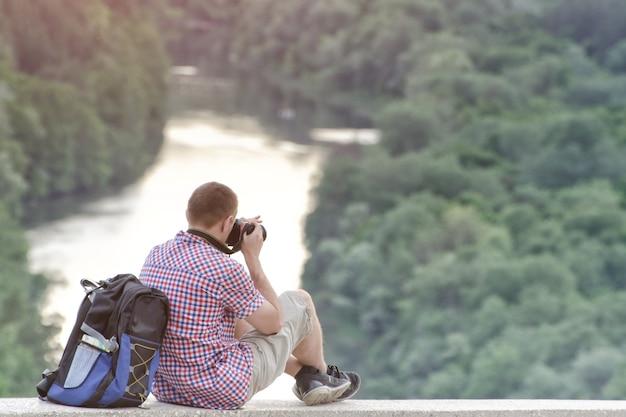 男は森と川の背景にある丘から写真を撮ります