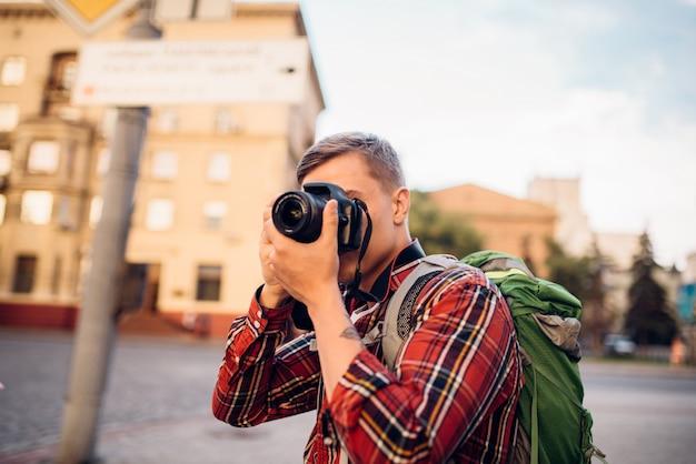 남자는 카메라에 도시의 관광 명소 사진을 찍습니다. 여름 여행, 관광을 통한 하이킹 모험