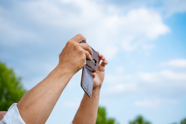 A man takes pictures on the phone against the sky during the day closeup without a face