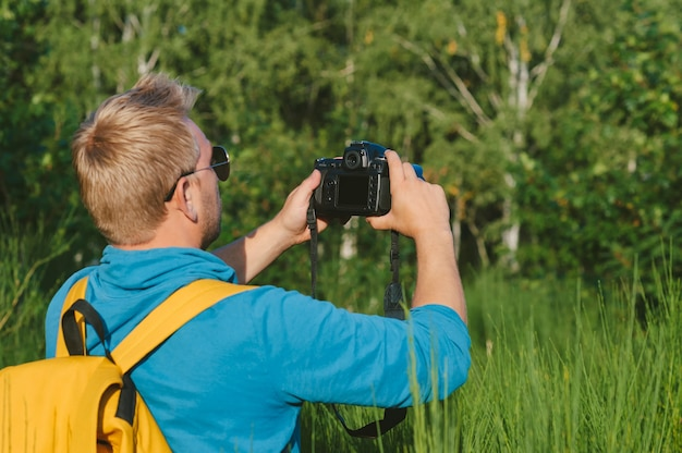 A man takes pictures with a slr camera in the forest. against the backdrop of beautiful greenery.