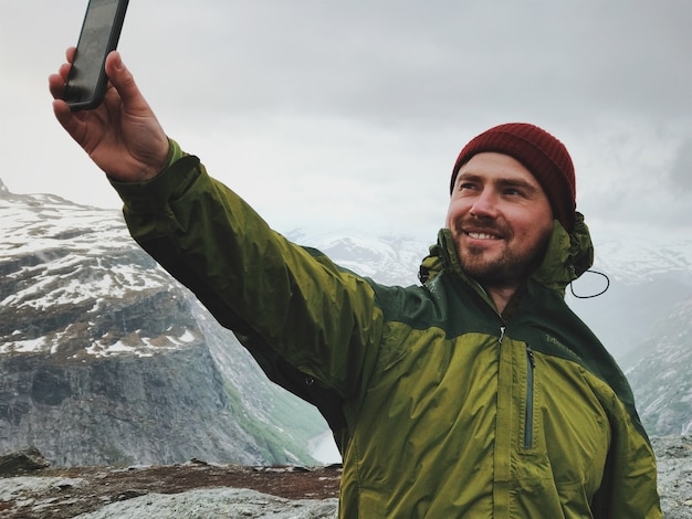 Man takes a selfie in the front of the mountains