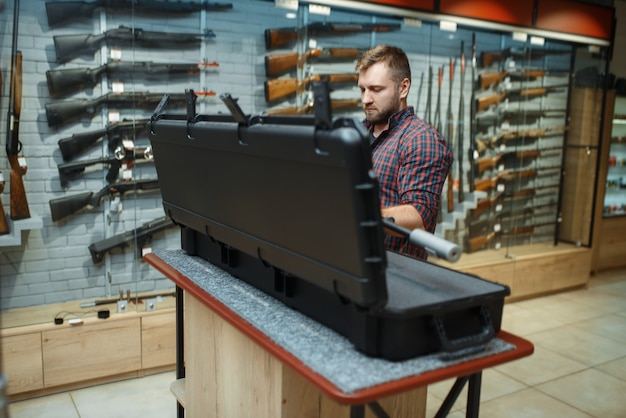 Man takes sniper rifle from the case in gun shop