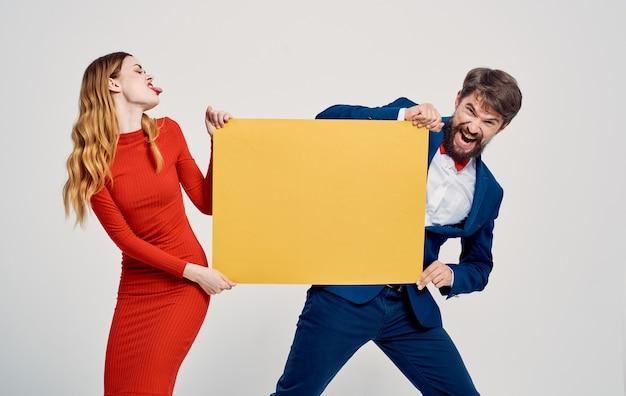 Мужчина берет макет из рук женщины, рекламируя эмоции веселья.