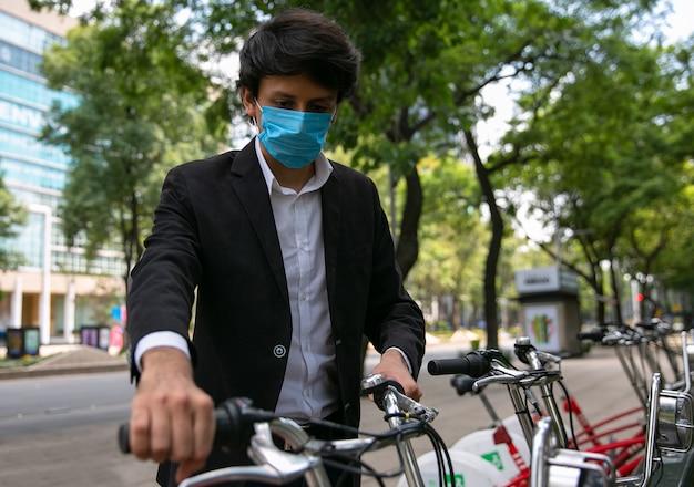通りで自転車に乗る男彼はウイルス予防のための保護マスクを着用しています