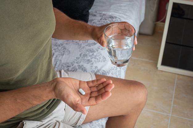 Мужчина принимает таблетку мелатонина, чтобы помочь ему уснуть. понятие о проблемах со сном или бессоннице