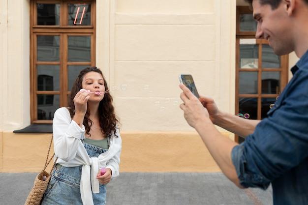 그의 귀여운 여자 친구의 사진을 찍는 남자
