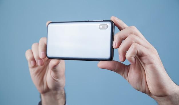スマートフォンで写真を撮る男。