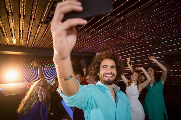 Человек, принимая селфи с мобильного телефона, а друзья танцуют на танцполе