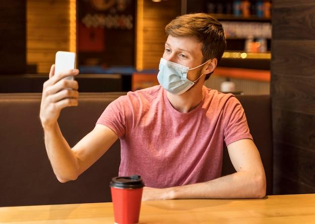 コーヒーショップでフェイスマスクを着用して自分撮りをしている男性