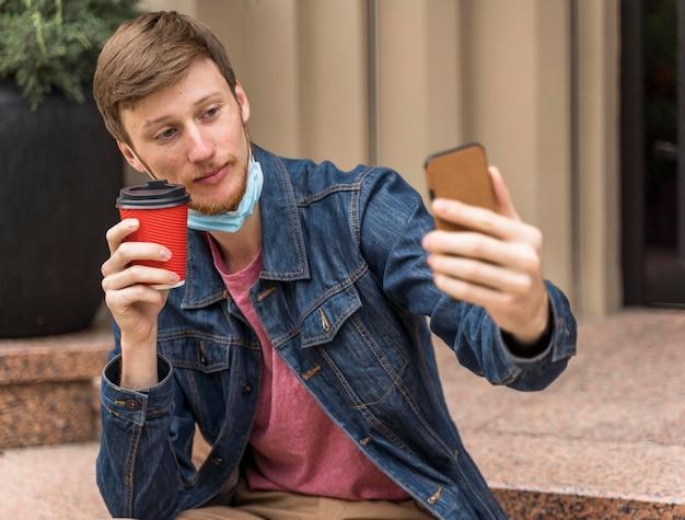 フェイスマスクを下にして自分撮りをしている男性