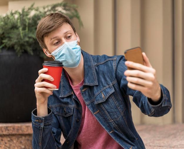 フェイスマスクをつけたまま自撮りする男