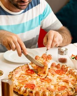 Человек берет кусок из колбасы пиццы