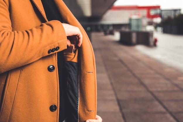 Мужчина берет бумажник из внутреннего кармана пальто