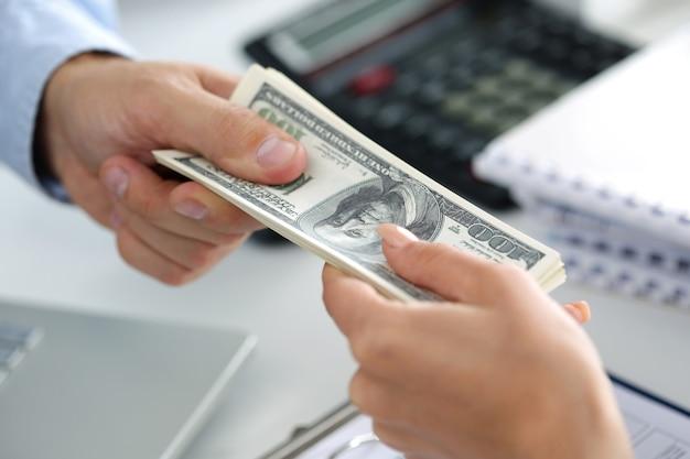 100ドル札のバッチを取る人。手をクローズアップ